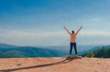 A person stands on the edge of a cliff overlooking greenery and a blue sky, holding their arms aloft and their fingers making peace signs