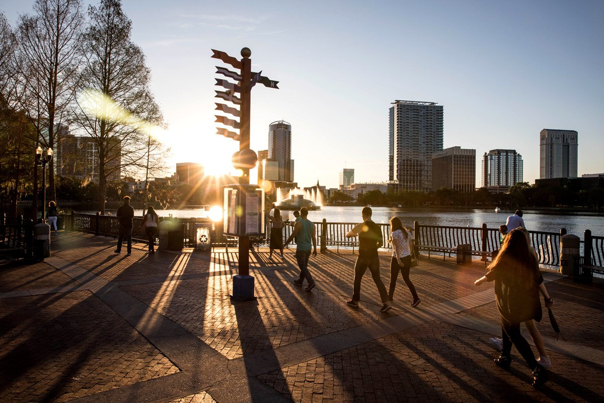 People walk alongside a lake and tall buildings.